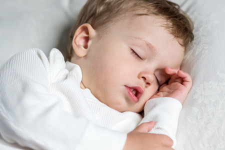 sweetly: Toddler boy sweetly asleep on a pillowon a white background