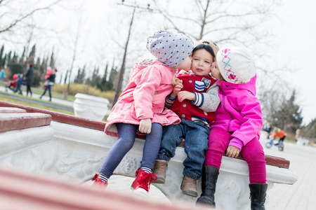 fun toddlers playing in the park sitting on the bench photo