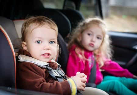 車の中で車の座席でかわいい小さな子供たち 写真素材