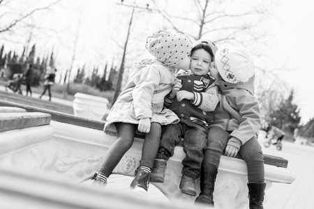 fun toddlers playing in the park sitting on the bench ( black and white ) photo