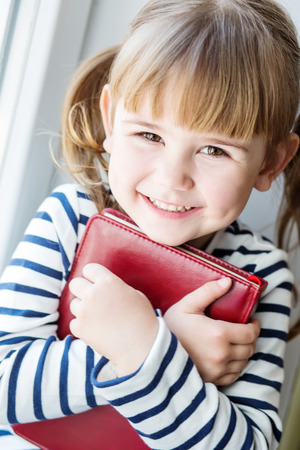 pretty little girl: happy little girl holding a book while sitting on the window