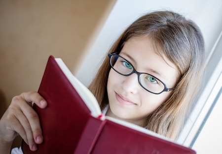 cute schoolgirl in glasses holding a book sitting on a window