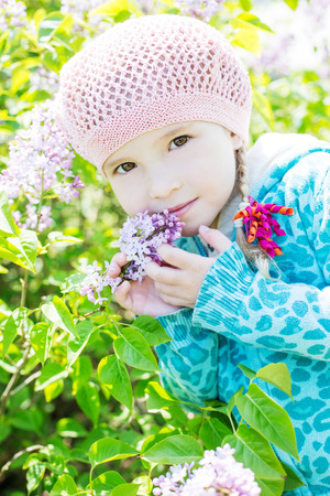 portrait of a little girl with lilac flowers photo