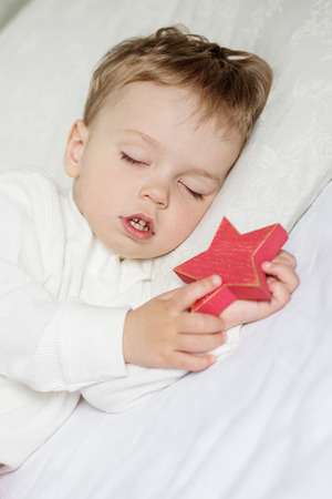 sweetly: Toddler boy sweetly sleeping with a toy on a white background