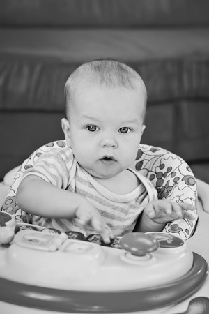 cute baby boy playing at home and looking at the camera ( black and white )