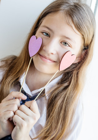 child charming: Portrait of a little girl with hearts on a white background Stock Photo