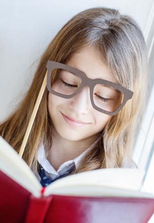 preteen model: cute schoolgirl in glasses holding a book sitting on a window