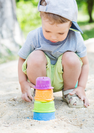 sandpit: Toddler boy playing in the sand in the summer