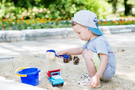 Peuter jongen spelen in het zand in de zomer