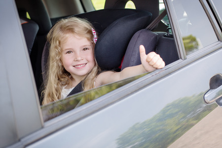 seat: happy little girl in the car summer