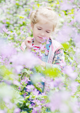 Spring portrait of a little girl in flowers photo
