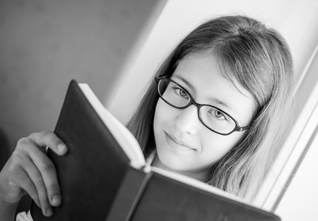 preteen model: cute schoolgirl in glasses holding a book sitting on a window ( black and white )