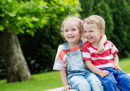 girl sit: Happy Toddler brother and sister hugging in summer