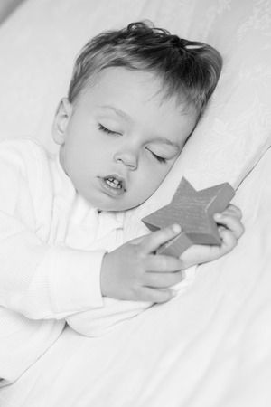 sweetly: Toddler boy sweetly sleeping with a toy ( black and white ) Stock Photo