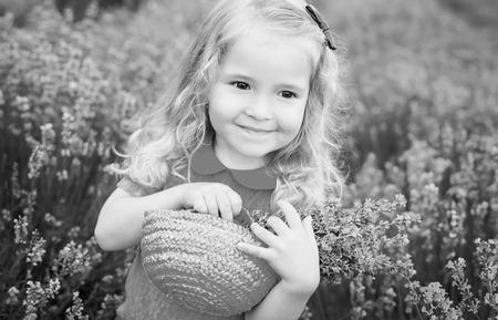 jolie petite fille: heureuse petite fille est dans un champ de lavande est titulaire d'un panier de fleurs (noir et blanc)