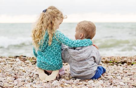 amigos abrazandose: pequeño hermano y hermana linda que juega en la playa