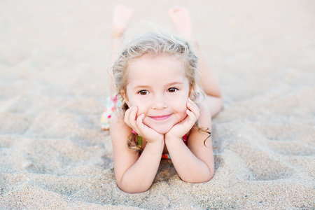 baby girl pink: Happy little girl lying on the sand on the beach Stock Photo