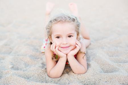 little girl beach: Happy little girl lying on the sand on the beach Stock Photo