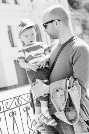 toddler walking: Father holding his son toddler walking outdoors ( black and white )