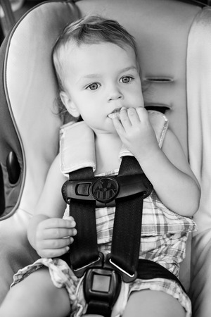 car seat: Happy Toddler boy in the car eating cookies  ( black and white ) Stock Photo