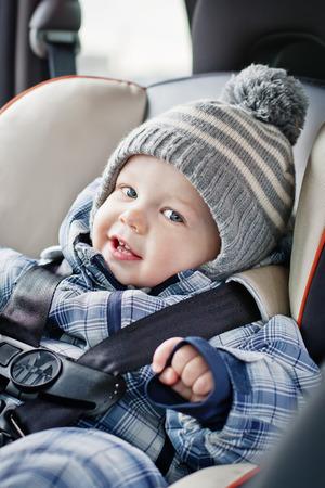 portrait happy baby boy sitting in the car seat
