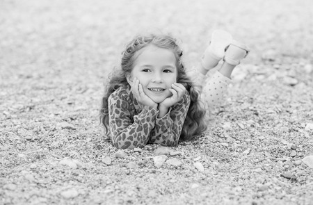 blak and white: Happy little girl lying on the pebbles on the beach ( black and white ) Stock Photo