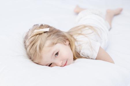 Sleepy cute little girl lying in bed Standard-Bild