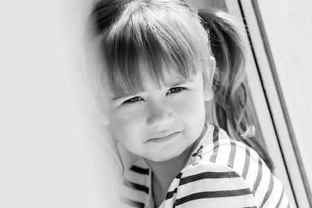 3 4 years: sad little girl sitting near the window  ( black and white )