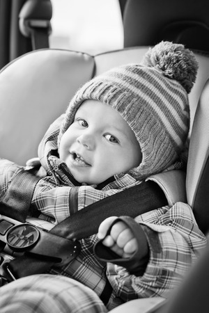 baby sit: portrait happy baby boy sitting in the car seat  (black and white) Stock Photo