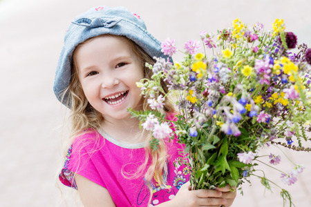 Happy toddler girl holding a bouquet of wildflowers