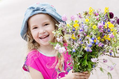 cute babies: Muchacha feliz del ni�o que sostiene un ramo de flores silvestres Foto de archivo