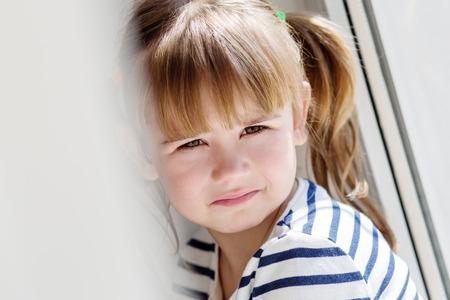 3 4 years: sad little girl sitting near the window