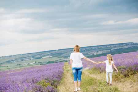 mum and child: happy mother with his little daughter in lavender field Stock Photo
