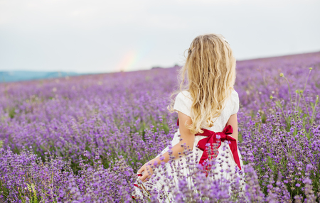sniffing: cute little girl is going to a lavender field