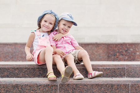friend hug: Happy toddler children sit on the steps outdoors