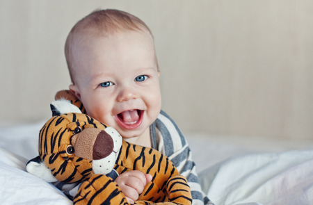 beautiful eyes: Happy baby in bed with a favorite toy Stock Photo