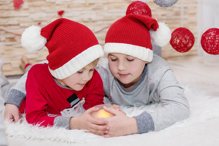 christmas hat: two little child santa embracing hold a candle Stock Photo