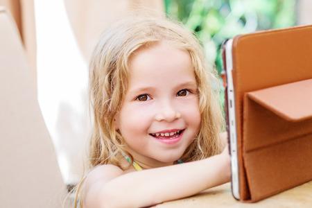 oudoors: Happy little girl using tablet computer oudoors