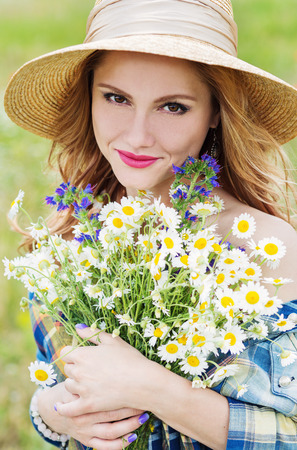 field of daisies: young woman with a bouquet of field daisies spring