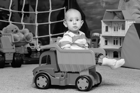 kiddy: Toddler boy sitting in the toy truck in the game room  ( black and white )