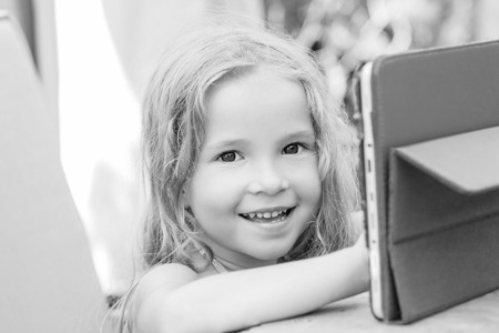 oudoors: Happy little girl using tablet computer oudoors ( black and white ) Stock Photo