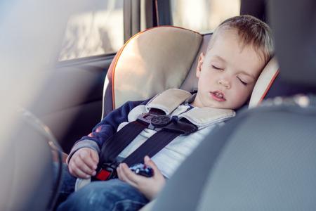 cute little boy sleeping in car seat Standard-Bild
