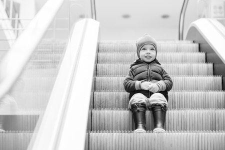 view of a staircase in a shop: Cute little child sitting on moving staircase in shop ( black and white )