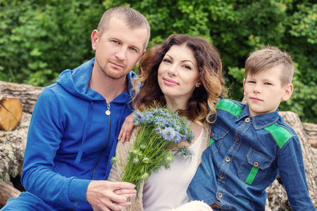 35 years old man: portrait of a young happy family outdoors in spring