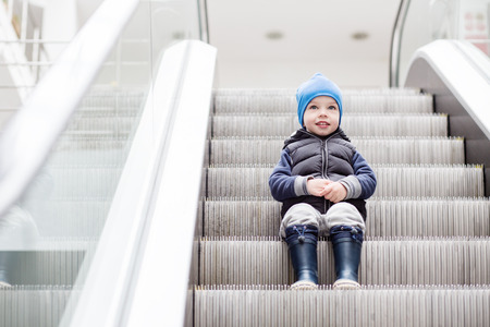 view of a staircase in a shop: Cute little child sitting on moving staircase in shop
