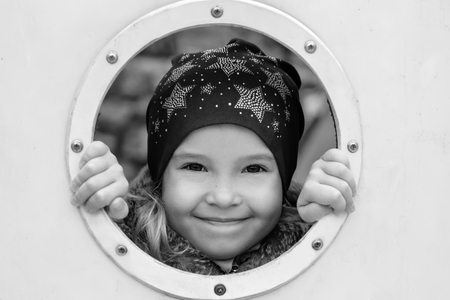 hide and seek: Happy little girl playing hide and seek outdoors ( black and white )