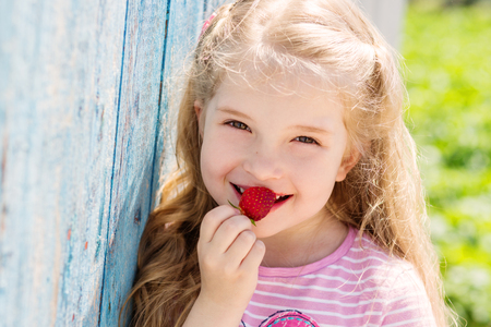Happy small child eating strawberries outdoors Stock Photo