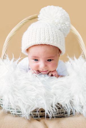 cute newborn baby in knitted cap on a beige background