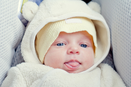 funny newborn baby in the car seat shows tongue Stock Photo