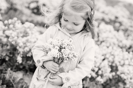 charming little girl smelling a bouquet of wildflowers (black and white)
